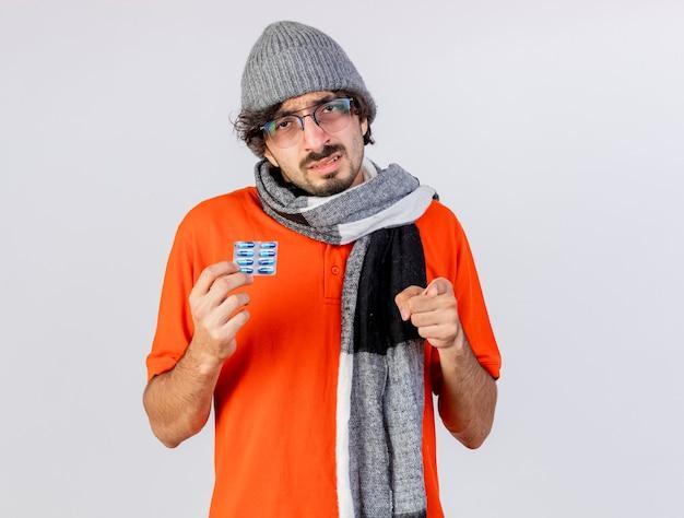 Zwakke jonge zieke man met bril, muts en sjaal met pak medische capsules kijken en wijzen naar voorzijde geïsoleerd op een witte muur