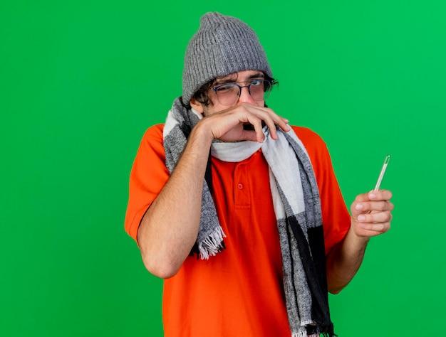 Zwakke jonge zieke man met bril, muts en sjaal met thermometer kijken naar voorkant afvegende neus met hand geïsoleerd op groene muur met kopie ruimte