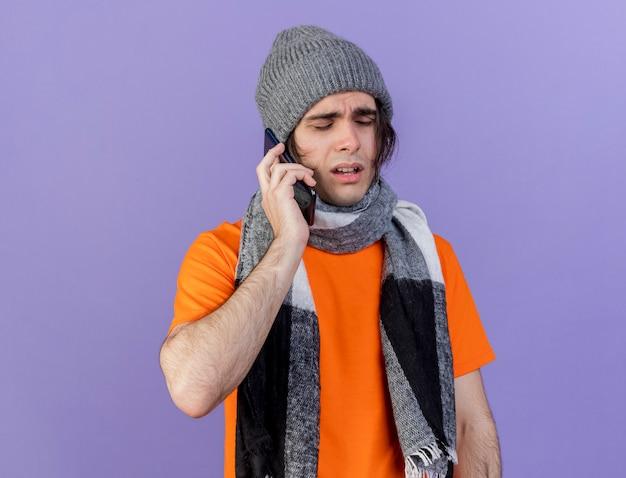 Zwakke jonge zieke man met muts met sjaal spreekt op telefoon geïsoleerd op paars