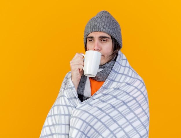 Zwakke jonge zieke man met winter hoed met sjaal het drinken van thee geïsoleerd op oranje