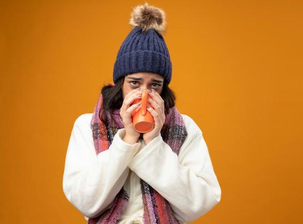 Zwakke jonge zieke vrouw die de muts en de sjaal van de gewaadsmuts en sjaal drinkt die kop thee drinkt die voorzijde bekijkt die op oranje muur wordt geïsoleerd