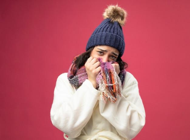 Zwakke jonge zieke vrouw die de muts en de sjaal van de gewaadwinter draagt ?? die mond behandelt met sjaal die voorzijde bekijkt die op roze muur wordt geïsoleerd