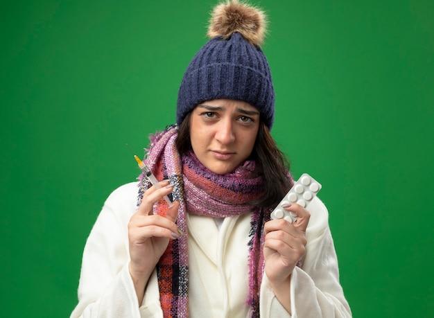 Zwakke jonge zieke vrouw die de muts van de gewaadwinter en sjaal draagt die spuit en pak tabletten bekijkt die voorzijde op groene muur bekijken