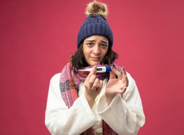 Zwakke jonge zieke vrouw die de muts van de gewaadwinter en sjaal draagt ?? die thermometer houdt die voorzijde bekijkt die op roze muur wordt geïsoleerd