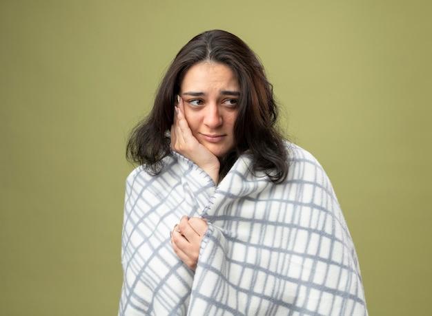 Zwakke jonge zieke vrouw die een gewaad draagt dat in een plaid is gewikkeld en naar de zijkant kijkt die een plaid vasthoudt die hand op het gezicht houdt geïsoleerd op olijfgroene muur