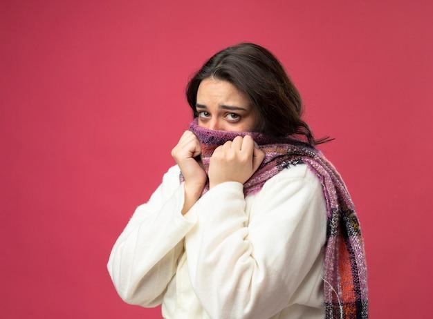Zwakke jonge zieke vrouw die een gewaad en een sjaal draagt die zich in profielweergave bevindt die mond bedekt met sjaal kijkt naar de voorkant en houdt de handen op de sjaal geïsoleerd op roze muur