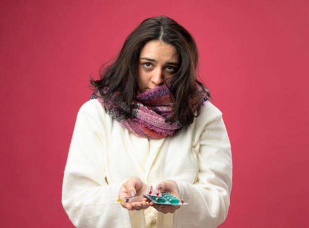 Zwakke jonge zieke vrouw die gewaad en sjaal draagt die spuit en verpakkingen van medische capsules houdt die voorzijde bekijken die op roze muur wordt geïsoleerd