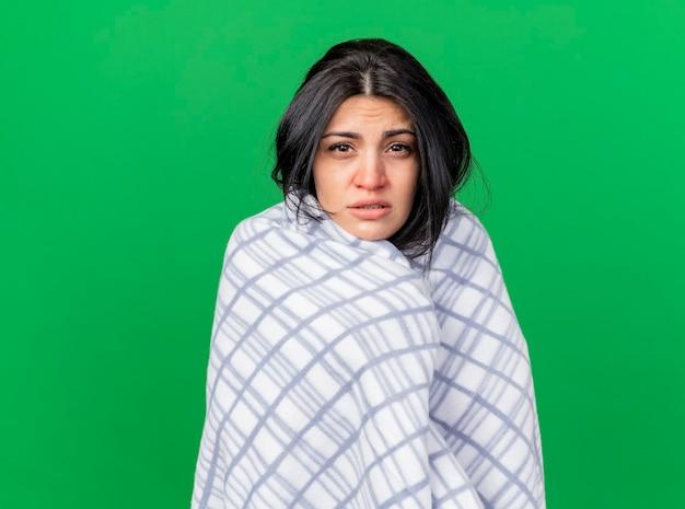 Zwakke jonge zieke vrouw gewikkeld in plaid kijken voorzijde geïsoleerd op groene muur