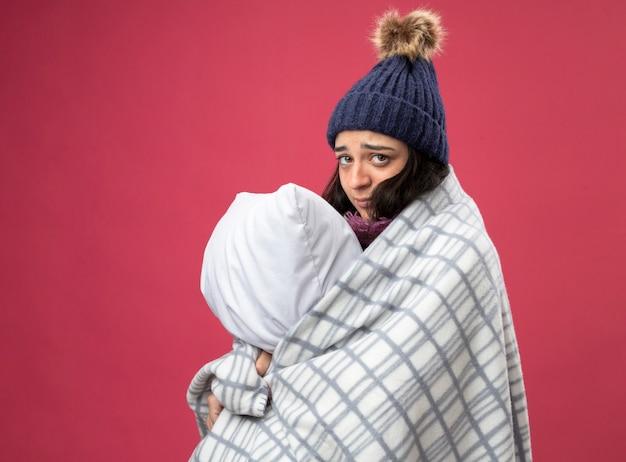 Zwakke jonge zieke vrouw met gewaad winter muts en sjaal gewikkeld in plaid staande in profielweergave knuffelen kussen kijken voorzijde geïsoleerd op roze muur