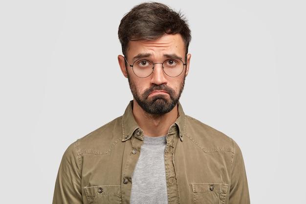 Zwakke, ongelukkige man voelt zich beledigd of beledigd, kromt de lippen en ziet er nors uit, voelt zich wanhopig en hulpeloos, heeft geen doelen of doelen in het leven, draagt een ronde bril en een shirt. negatieve emoties