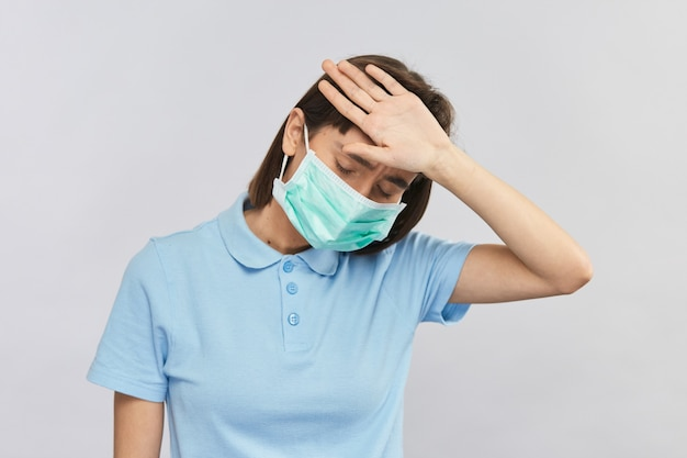 Zwakke vrouw met ziekte controleert de lichaamstemperatuur op het voorhoofd en draagt een steriel masker om coronavirus te voorkomen