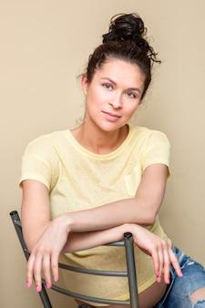 Zwanger gelukkig meisje in geel t-shirt en spijkerbroek zit op stoel