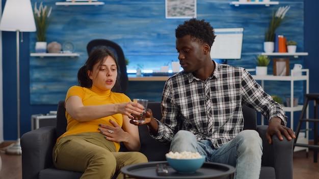 Zwanger interraciaal koppel zittend op de bank in de woonkamer