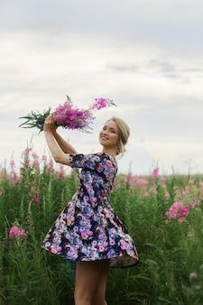 Zwanger meisje die op gebied van bloemenwilgeroosje lopen, vrouw die en bloemen glimlachen plukken.