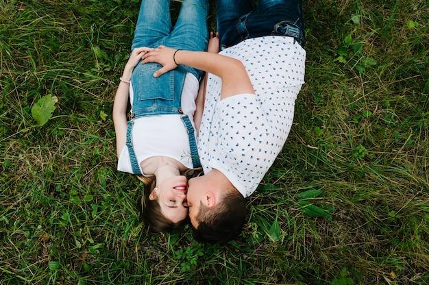 Zwanger meisje en haar man knuffelen graag, houden elkaars hand vast, liggen op de buik, liggen op het gras in de buitenlucht in de tuin