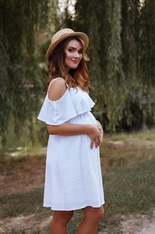 Zwanger meisje in een hoed en witte zomerjurk in de avond in het park