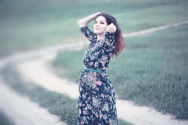 Zwanger meisje in een jurk in de natuur op een wandeling
