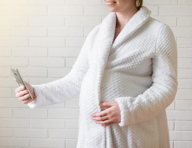 Zwanger meisje in een zacht gewaad gebruikt een smartphone om te communiceren.