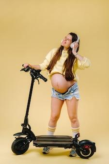 Zwanger meisje in gele kleding en koptelefoon op een elektrische scooter op een afgelegen gele achtergrond.