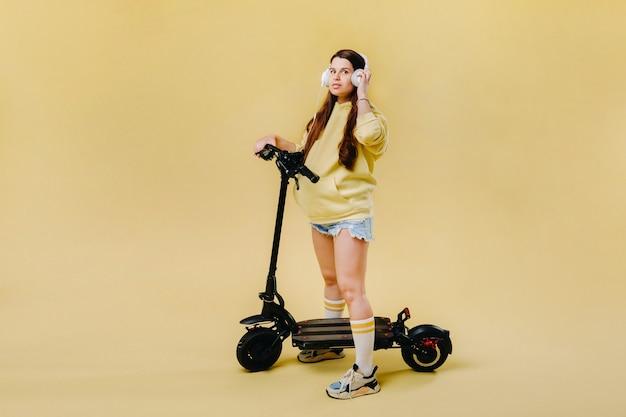 Zwanger meisje in gele kleding en koptelefoon op een elektrische scooter op een geïsoleerde gele achtergrond