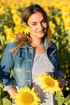 Zwanger meisje in zonnebloemen, gelukkig meisje dat op de baby wacht