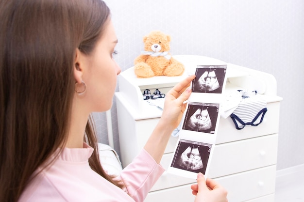 Zwanger meisje is op zoek naar een echo. verwachting van een kind, moederschap.