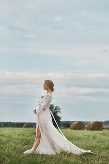 Zwanger meisje loopt in een veld in de buurt van hooibergen in een lange witte jurk, een vrouw glimlacht en houdt haar handen voor haar buik
