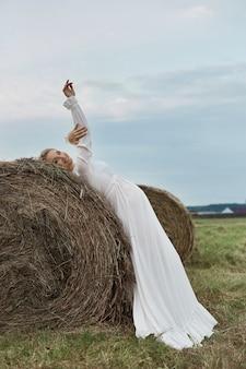 Zwanger meisje loopt in een veld in de buurt van hooibergen in een lange witte jurk, een vrouw glimlacht en houdt haar handen voor haar buik.