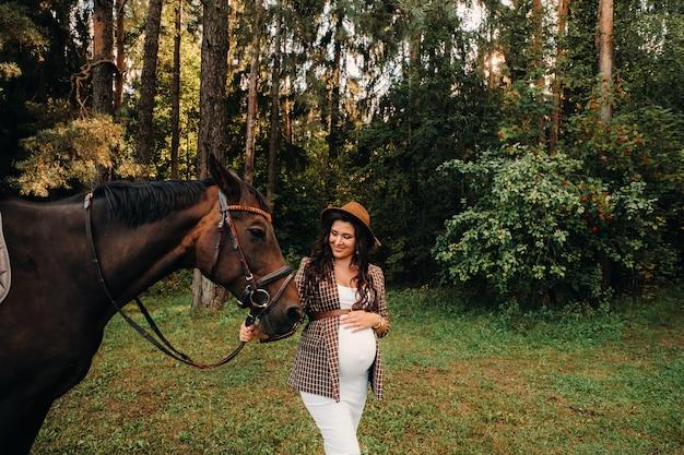 Zwanger meisje met een dikke buik in een hoed naast paarden in het bos in de natuur