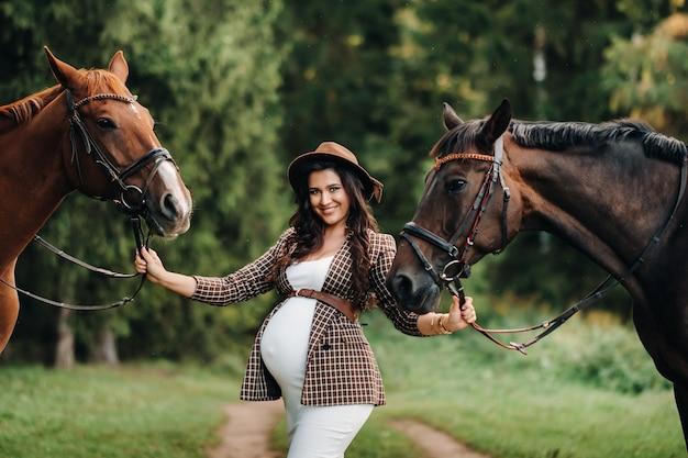 Zwanger meisje met een grote buik in een hoed naast paarden in het bos in de natuur. stijlvol meisje in witte kleren en een bruine jas.