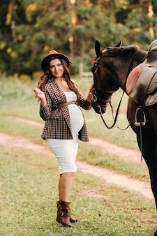 Zwanger meisje met een grote buik in een hoed naast paarden in het bos in de natuur. stijlvolle zwangere vrouw in de bruine jurk met de paarden.