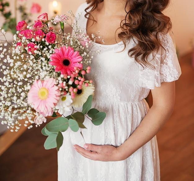 Zwanger meisje op een lichte achtergrond met bloemen