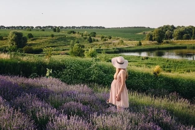 Zwanger meisjesblonde in een beige kleding en een strohoed. lavendel veld. in afwachting van een kind. het idee van een fotoshoot. loop bij zonsondergang. toekomstige moeder. mand met bloemen.