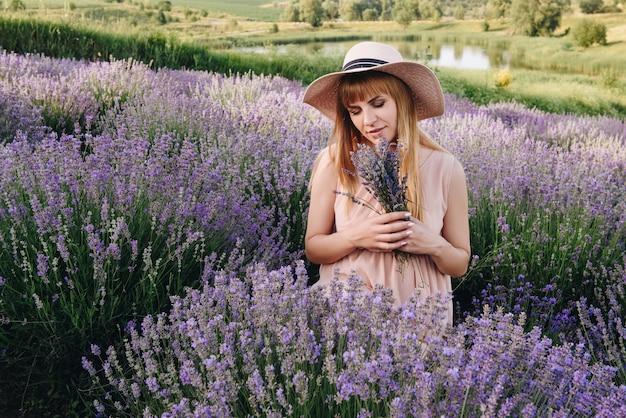 Zwanger meisjesblonde in een beige kleding en een strohoed. lavendel veld. in afwachting van een kind. het idee van een fotoshoot. loop bij zonsondergang. toekomstige moeder. portret. boeket bloemen.