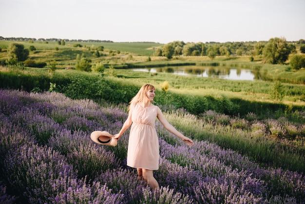 Zwanger meisjesblonde in een beige kleding en een strohoed. lavendel veld. in afwachting van een kind. het idee van een fotoshoot. loop bij zonsondergang. toekomstige moeder.