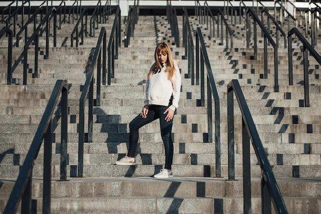 Zwanger meisjesblonde in jeans en hoodie. sportieve stijl. wees fit. in de grote stad. lang haar. 9 maanden wachten. geluk om moeder te zijn. bewaak de gezondheid.