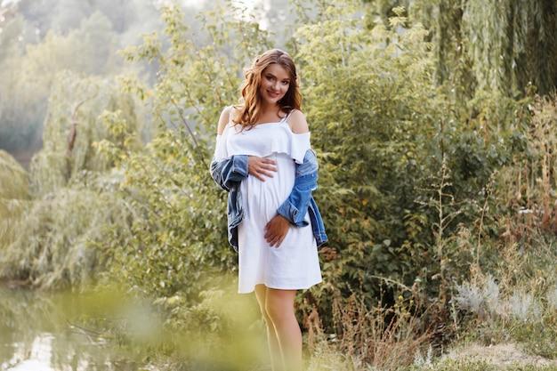 Zwanger omhelst haar buik en glimlacht. prachtig park