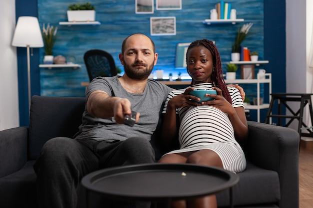 Zwanger paar die tussen verschillende rassen camera kijken die televisie op bank kijken. pov van partners van gemengd ras met zwangerschap die ontspannen terwijl ze popcorn eten en de afstandsbediening van de tv gebruiken.