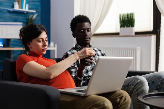 Zwanger paar die tussen verschillende rassen ontspannen en technologie gebruiken. mensen van gemengd ras die een kind verwachten, een blanke vrouw met een moderne laptop en een zwarte vader van een baby die naar het scherm van het apparaat kijkt