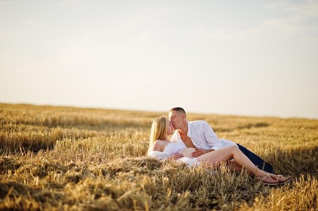 Zwanger paar op kroongebied bij witte ondergoedkleren op zonsondergang