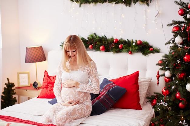 Zwanger vrouwenportret, nieuwjaarvibes. charmante blonde verwachtende vrouw