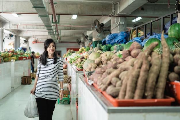 Zwangere aziatische jonge vrouw die dragend plastic zak bevindt zich