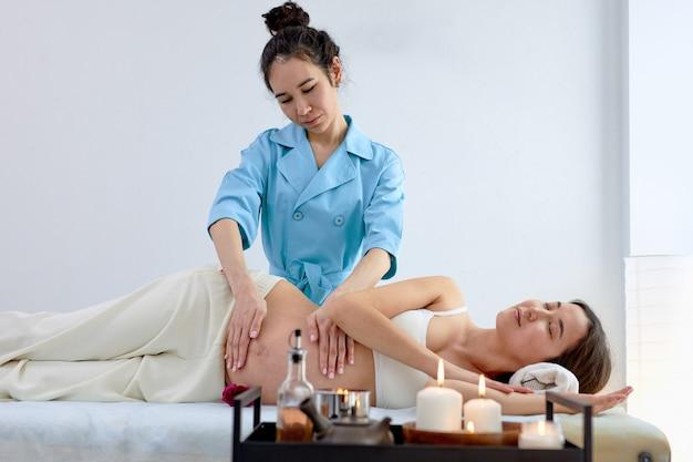 Zwangere aziatische jonge vrouw liggend op bed en met ontspannende oosterse prenatale massage op buik, genieten van professionele massage, voorbereiden op de bevalling, spieren trainen