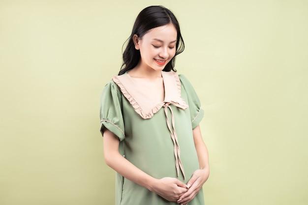 Zwangere aziatische vrouw die zich gelukkig voelt en uitkijkt naar de bevalling
