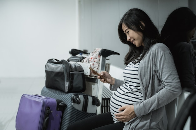 Zwangere aziatische vrouwen gebruiken smartphones voor videogesprekken