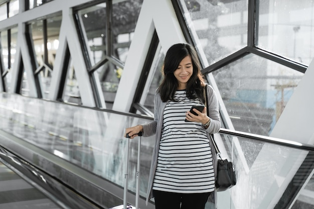 Zwangere aziatische vrouwen zien mobieltjes als ze door de roltrap lopen