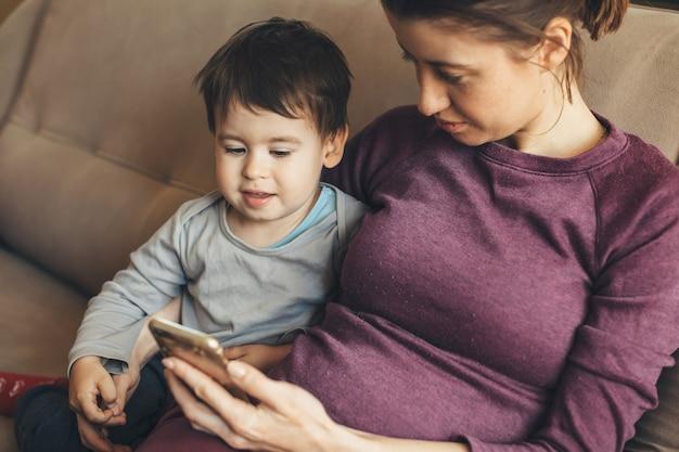 Zwangere blanke vrouw en haar zoontje kijken aan de telefoon zittend geïsoleerd thuis op de bank