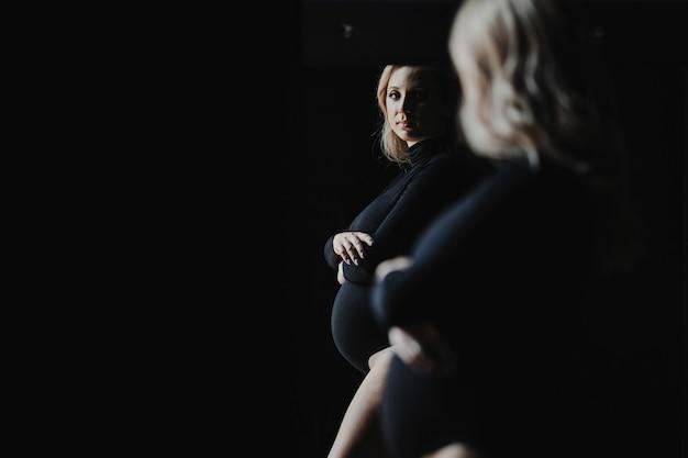 Zwangere blonde vrouw in een zwarte bodysuit staat in de buurt van een spiegel en kijkt naar haar spiegelbeeld