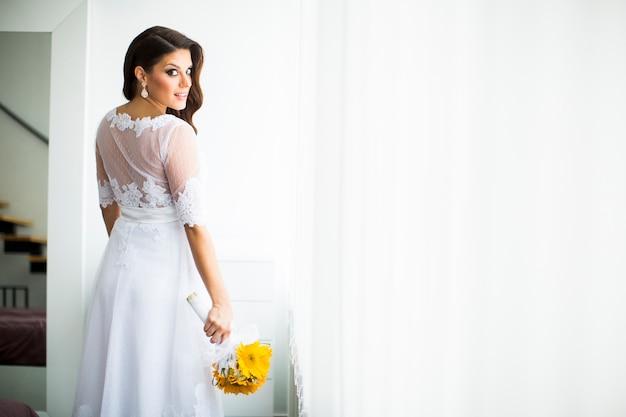 Zwangere bruid met een boeket van zonnebloemen