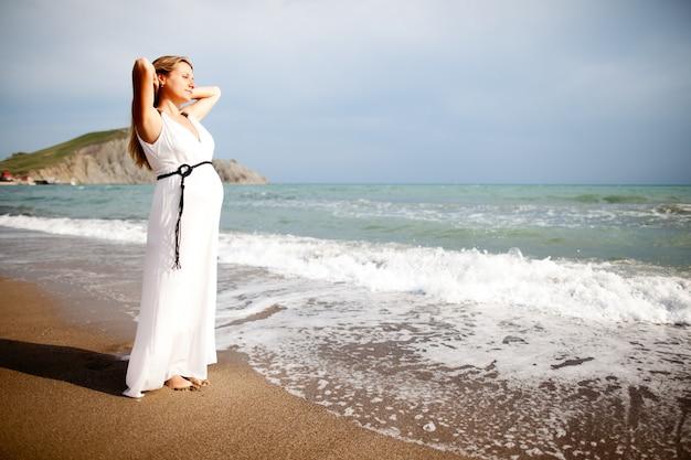 Zwangere dame die zich op strand dichtbij overzees bevindt